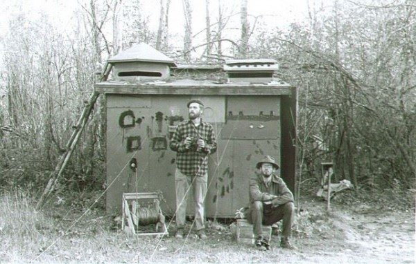 Helmut Mueller (left) and Dan Berger (right) in front of the original Cedar Grove Ornithological Research Station hawk trapping blind in 1950. Image courtesy of the Cedar Grove Ornithological Research Station archives, photo taken remotely by Helmut Mueller.